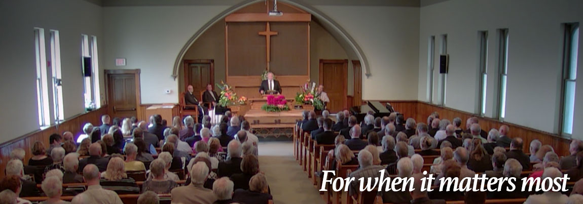 A wide shot of a funeral serive in a church videotaped by Hawkeye Films